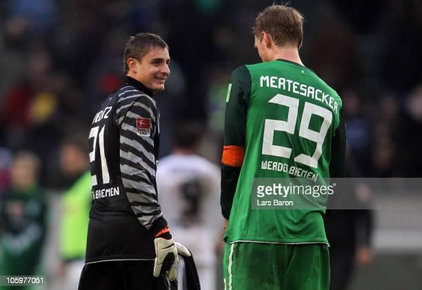 Goalkeeper Sebastian Mielitz of Bremen smiles with team mate Per Mertesacker after winning the Bundesliga match between Borussia Moenchengladbach and...