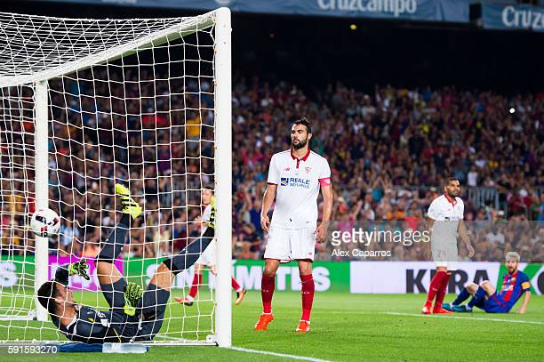 Goalkeeper Sergio Rico of Sevilla FC falls inside the goal and his teammate Vicente Iborra looks on as Lionel Messi of FC Barcelona scores his team's...