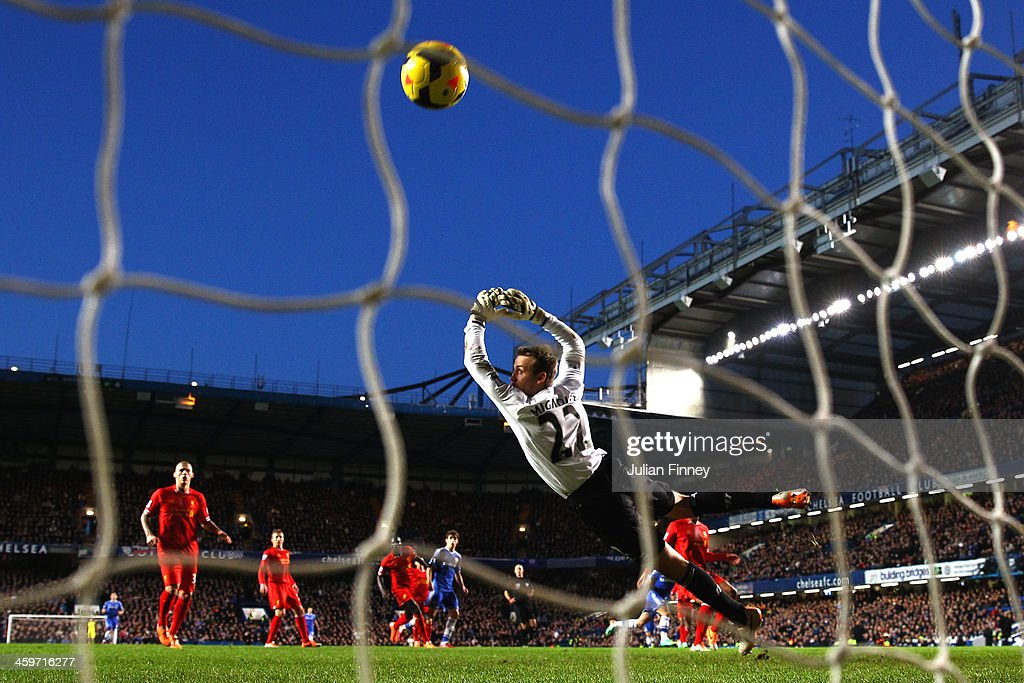 Goalkeeper Simon Mignolet of Liverpool dives in vain as Eden Hazard of Chelsea scores his team's first goal during the Barclays Premier League match between Chelsea and Liverpool at Stamford Bridge on December 29, 2013 in London, England.