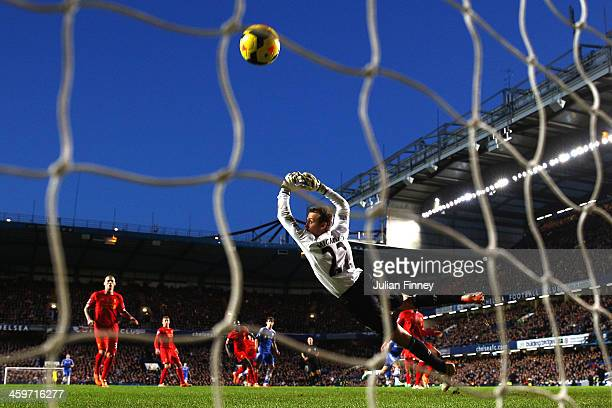 Goalkeeper Simon Mignolet of Liverpool dives in vain as Eden Hazard of Chelsea scores his team's first goal during the Barclays Premier League match...