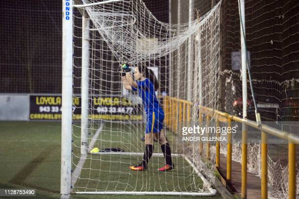 A goalkeeper stands under the goal's net during a training session at the Anorga KKE football school in the Spanish Basque city of San Sebastian on...