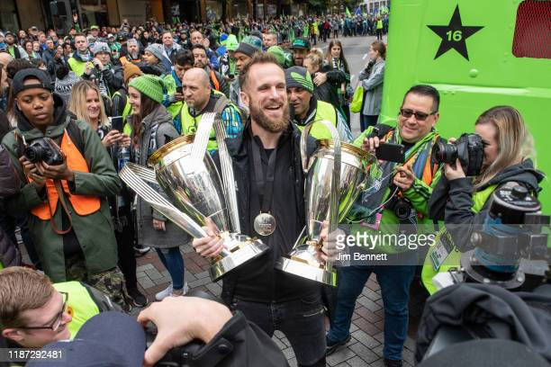 Goalkeeper Stefan Frei of the Seattle Sounders holds the 2016 and 2019 MLS Cup trophies in the street during the Seattle Sounders MLS Cup victory...
