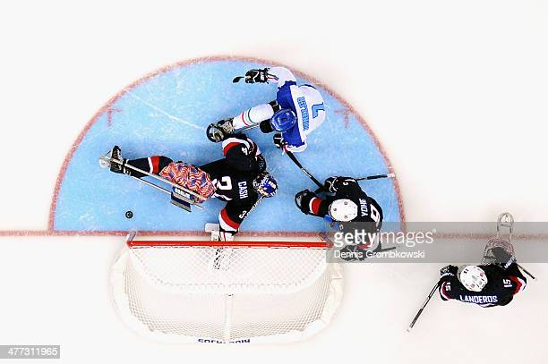 Goalkeeper Steve Cash of the United States stretches for the puck under the pressure of Werner Winkler of Italy during the Ice Sledge Hockey...