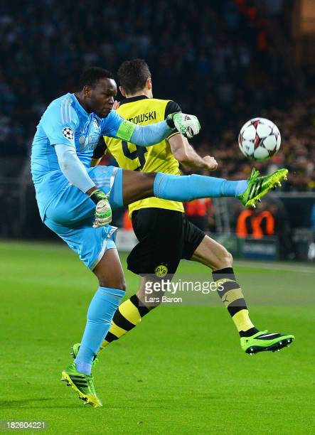Goalkeeper Steve Mandanda of Olympique Marseille clears past Robert Lewandowski of Borussia Dortmund during the UEFA Champions League Group F match...
