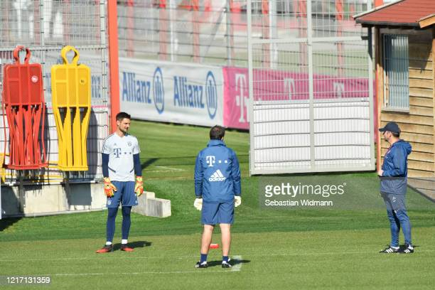 Goalkeeper Sven Ulreich goalkeeping coach Toni Tapalovic and head coach HansDieter Flick of Bayern Muenchen talk during a training session at...