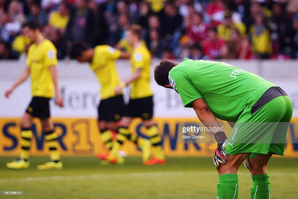 Goalkeeper Sven Ulreich of Stuttgart reacts as Marco Reus of Dortmund celebrates his team's third goal with team mates during the Bundesliga match between VfB Stuttgart and Borussia Dortmund at Mercedes-Benz Arena on March 29, 2014 in Stuttgart, Germany.