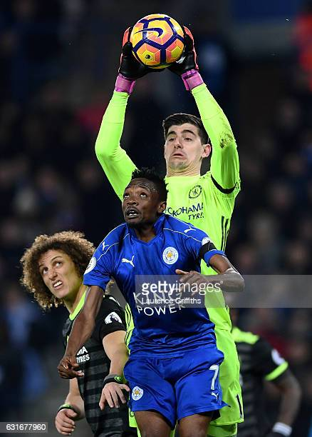 Goalkeeper Thibaut Courtois of Chelsea claims a cross under pressure from Ahmed Musa of Leicester City during the Premier League match between...