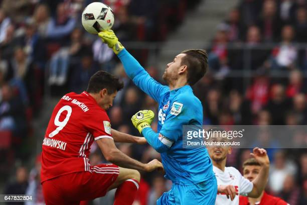 Goalkeeper Thomas Kessler of Koeln punches the ball away from Robert Lewandowski of Bayern Munich during the Bundesliga match between 1 FC Koeln and...