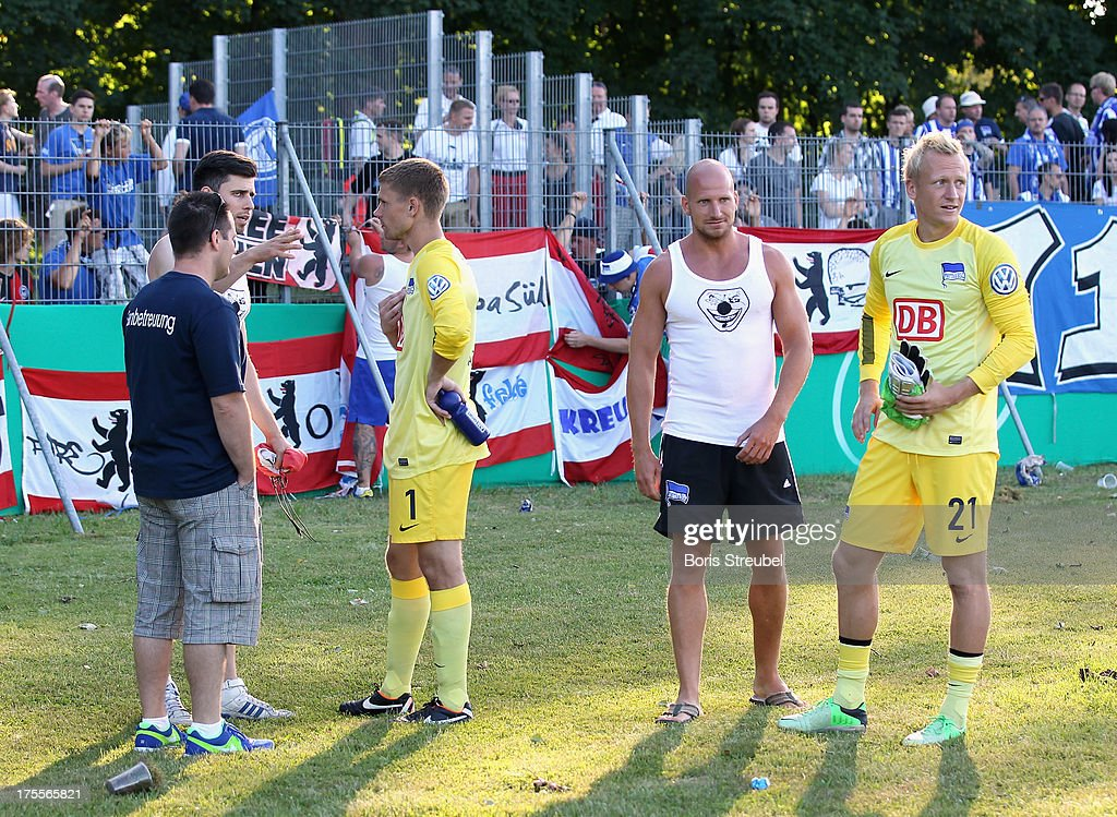 Goalkeeper Thomas Kraft (2nd L) and Sascha Burchert (R) of Hertha BSC talk to upset fans after the DFB Cup first round match between VfR Neumuenster and Hertha BSC Berlin at Gruemmi-Arena on August 4, 2013 in Neumuenster, Germany.
