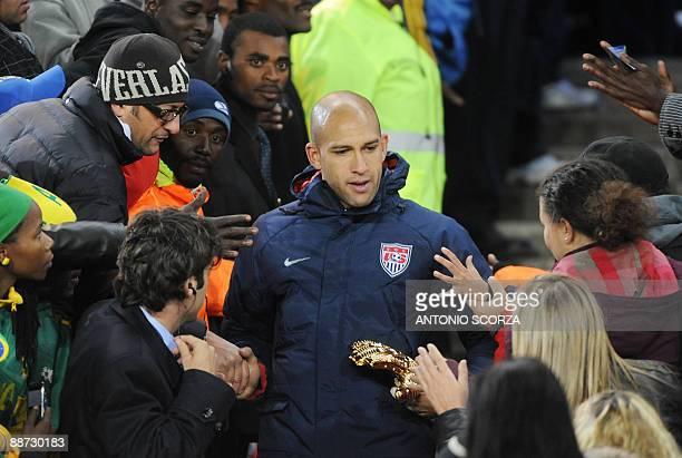 US goalkeeper Tim Howard holding a golden glove is congratulated by supporters after the Fifa Confederations Cup final football match United States...