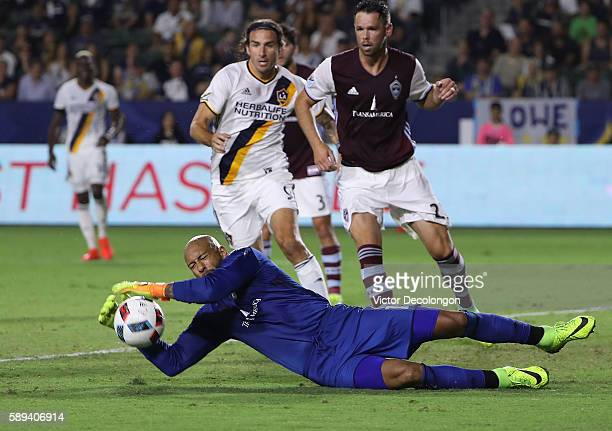Goalkeeper Tim Howard of Colorado Rapids makes a save as Alan Gordon of Los Angeles Galaxy and Bobby Burling of Colorado Rapids look for the rebound...