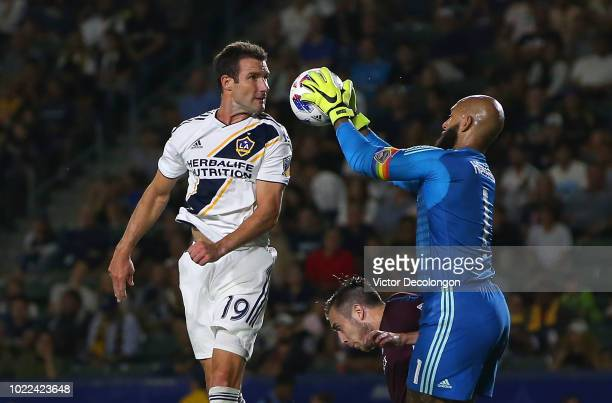 Goalkeeper Tim Howard of Colorado Rapids makes a save as Chris Pontius of Los Angeles Galaxy tries for the header during the second half of their MLS...