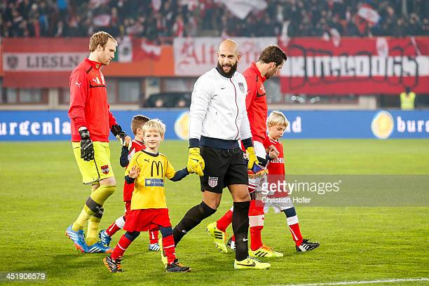 Goalkeeper Tim Howard of USA walks onto the pitch while holding hands with a ball boy prior to the International friendly match between Austria and...