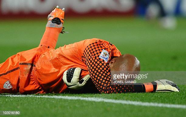US goalkeeper Tim Howard reacts in pain after clashing with a player during the 2010 World Cup group C first round football match between the USA and...