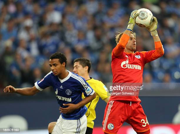 Goalkeeper Timo Hildebrand of Schalke controls the ball near Joel Matip and Robert Lewandowski of Dortmund during the Bundesliga match between...
