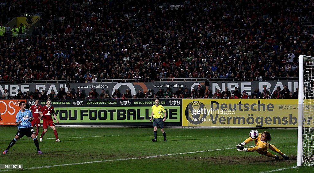 Goalkeeper Tobias Sippel of Kaiserslautern parries a penalty by Alexander Ludwig (L) of Muenchen during the Second Bundesliga match between 1. FC Kaiserslautern and 1860 Muenchen at the Fritz-Walter Stadium on March 29, 2010 in Kaiserslautern, Germany.