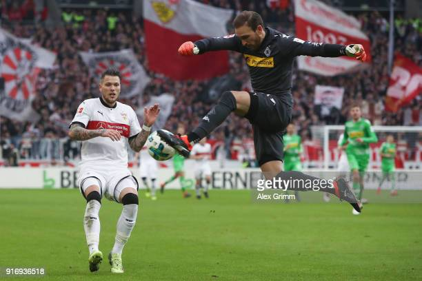 Goalkeeper Tobias Sippel of Moenchengladbach clears the ball ahead of Daniel Ginczek of Stuttgart during the Bundesliga match between VfB Stuttgart...