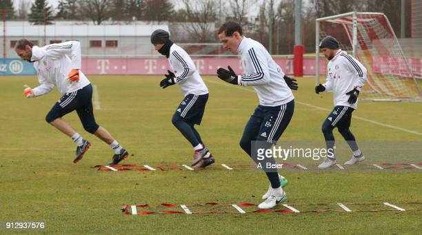 Goalkeeper Tom Starke James Rodriguez Sebastian Rudy and Juan Bernat of FC Bayern Muenchen warm up during a training session at the club's Saebener...
