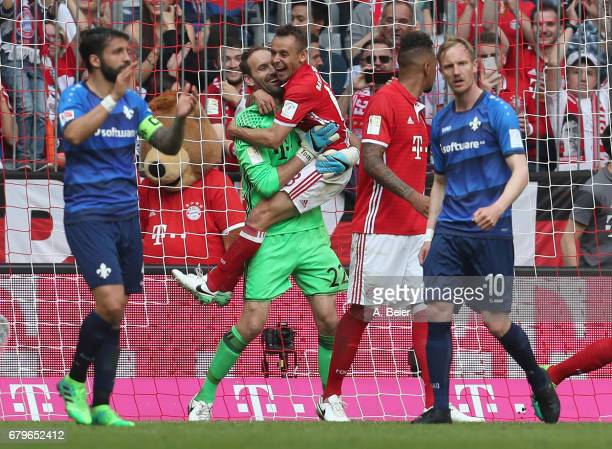 Goalkeeper Tom Starke of FC Bayern Muenchen celebrates a saved penalty shot together with his teammate Rafinha during the Bundesliga match between...