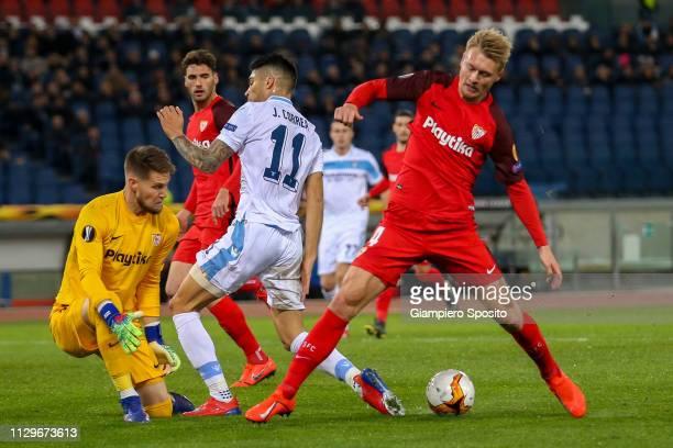 Goalkeeper Tomas Vaclik and Simon Kjaer of Sevilla challenge Joaquin Correa of Lazio during the UEFA Europa League Round of 32 First Leg match...