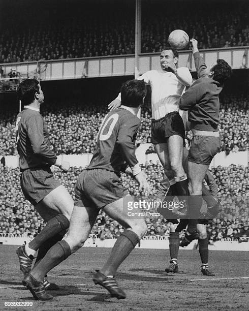 Goalkeeper Tommy Lawrence of Liverpool attempts to punch the ball clear from Spurs forward Alan Gilzean as number 10 Tommy Smith and number 5 Ron...