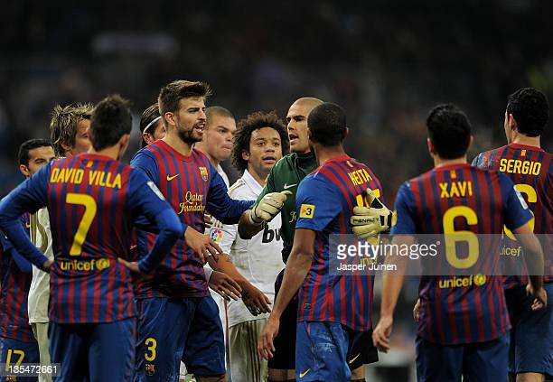Goalkeeper Victor Valdes and Gerard Pique of FC Barcelona hold back their teammate Seydou Keita during a scuffle in the la Liga match between Real...