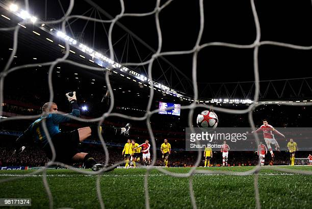 Goalkeeper Victor Valdes of Barcelona dives in vain as Cesc Fabregas of Arsenal scores a penalty to level the scores at 22 during the UEFA Champions...