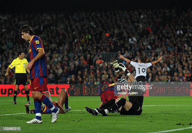 Goalkeeper Victor Valdes of Barcelona sits dejected on the pitch as he reacts with his teammate Maxwell and others to Pablo Hernandez of Valencia...
