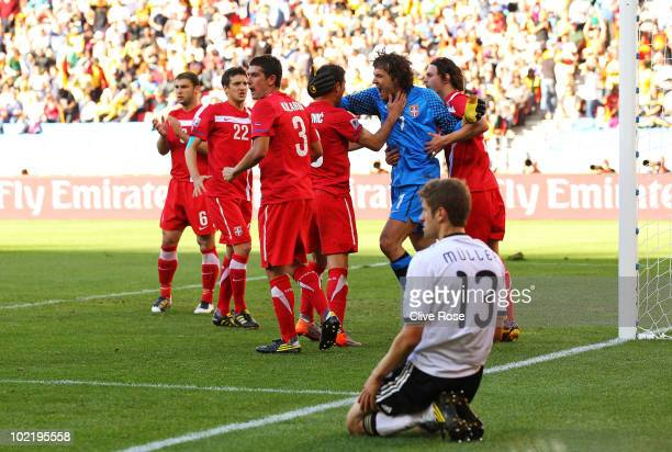 Goalkeeper Vladimir Stojkovic of Serbia celebrates with team mates after he saved a penalty as Thomas Mueller of Germany looks on during the 2010...