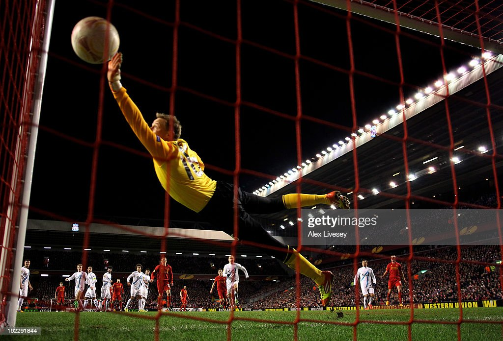 Goalkeeper Vyacheslav Malafeev of Zenit dives in vain as Luis Suarez of Liverpool scores a goal from a second half free kick during the UEFA Europa League round of 32 second leg match between Liverpool FC and FC Zenit St Petersburg at Anfield on February 21, 2013 in Liverpool, England.
