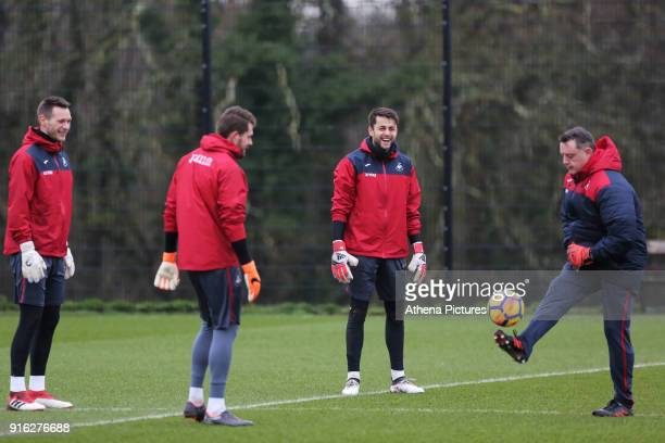 Goalkeepers Erwin Mulder Kristoffer Nordfeldt and Lukasz Fabianski warm up with Tony Roberts goalkeeping coach during the Swansea City Training and...