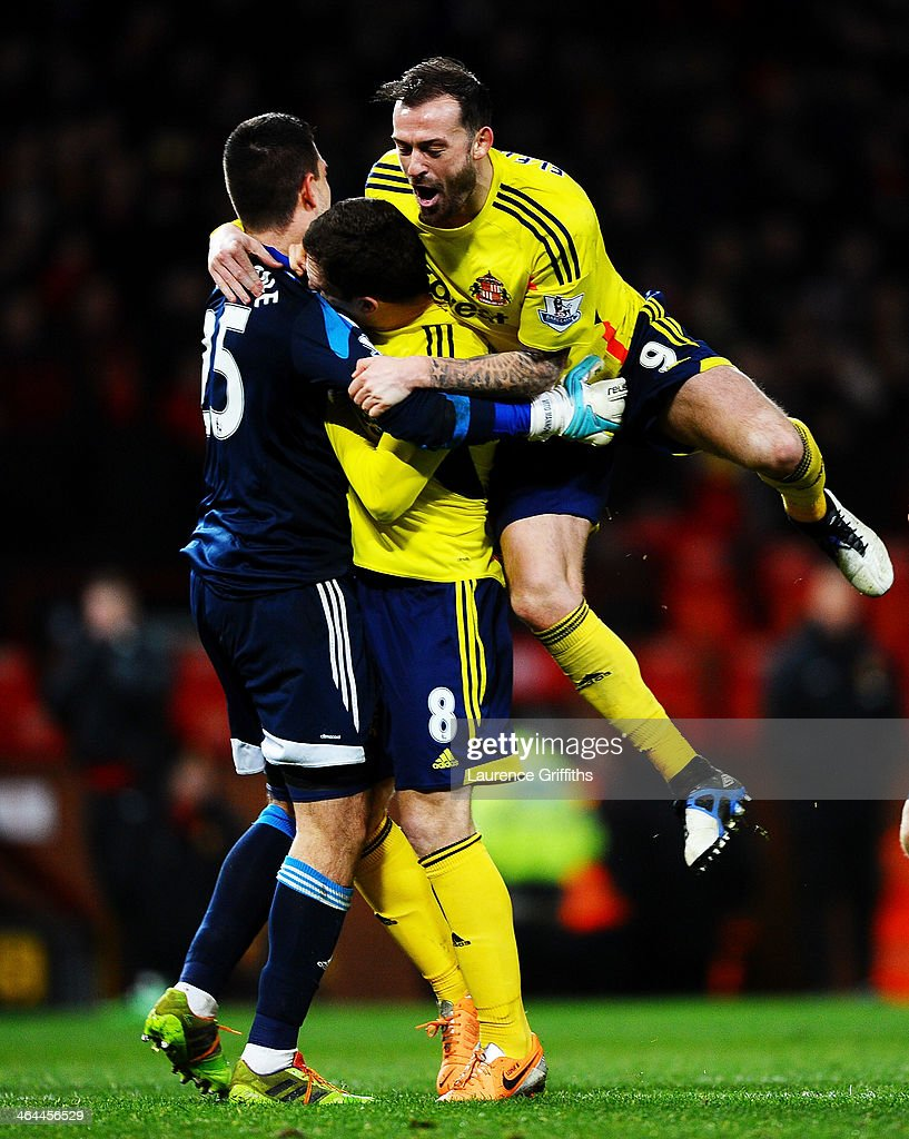 GoalkeeperVito Mannone of Sunderland is congratulated by teammates Craig Gardner and Steven Fletcher after saving the penalty from Rafael Da Silva of Manchester United to win the match during the Capital One Cup semi final, second leg match between Manchester United and Sunderland at Old Trafford on January 22, 2014 in Manchester, England.