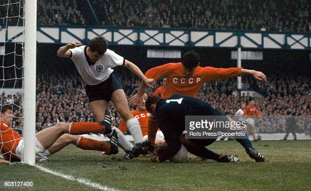 A goalmouth scramble as the Soviet Union goalkeeper Lev Yashin falls on the ball to thwart Lothar Emmerich of West Germany during the World Cup...