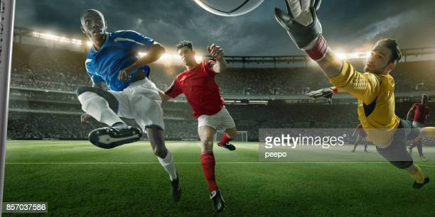 goalmouth view of soccer player scoring with mid-air volley - portiere posizione sportiva foto e immagini stock