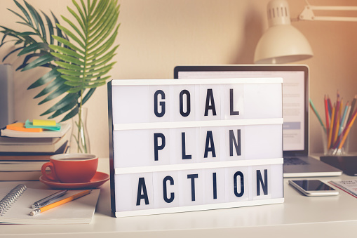 Goal,plan,action text on light box on desk table in home office 1153879953