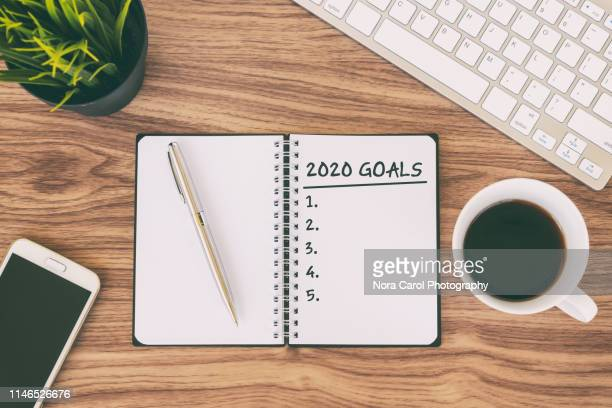 2020 goals text on note pad - aspiraties stockfoto's en -beelden
