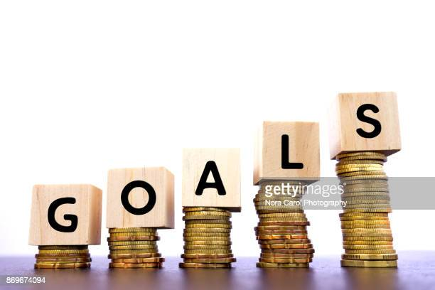 Goals Word on Wood Block on Top of Coins Stack