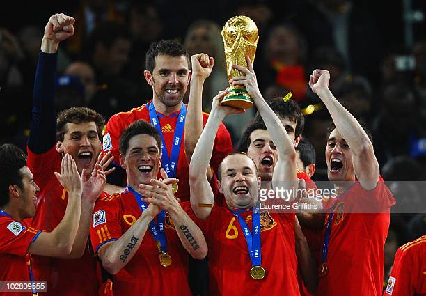 Goalscorer Andres Iniesta of Spain lifts the World Cup trophy as the Spain team celebrate victory following the 2010 FIFA World Cup South Africa...