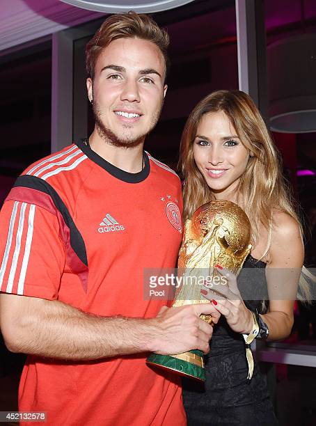 Goalscorer Mario Gotze of Germany and girlfriend AnnKathrin Brommel pose with the World Cup trophy as he celebrates with teammates at a party after...