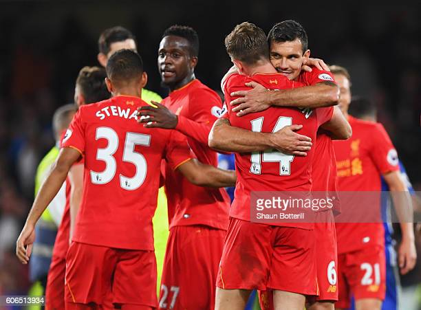 Goalscorers Jordan Henderson and Dejan Lovren of Liverpool celebrate victory after the Premier League match between Chelsea and Liverpool at Stamford...