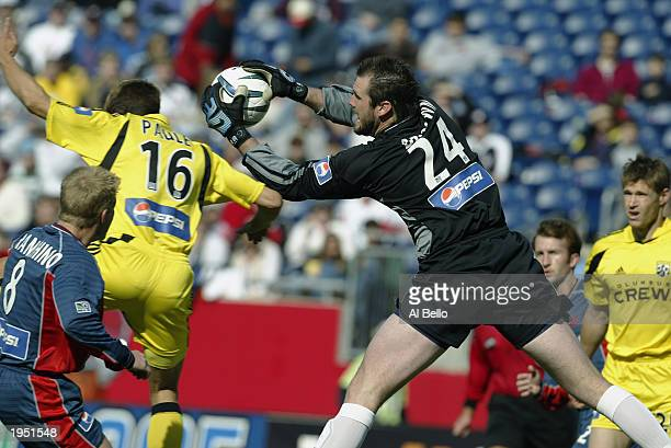 Goaltender Adin Brown of the the New England Revolution makes a save against midfielder Ross Paule of the Columbus Crew during the game at Gillette...
