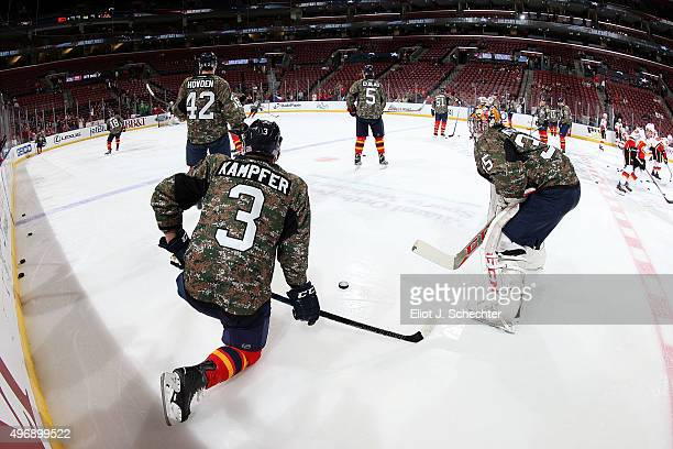 Goaltender Al Montoya of the Florida Panthers and teammate Steven Kampfer stretch on the ice prior to the start of the game against the Calgary...