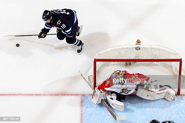 Goaltender Al Montoya of the Florida Panthers looks behind the net as Bryan Little of the Winnipeg Jets plays the puck during second period on...