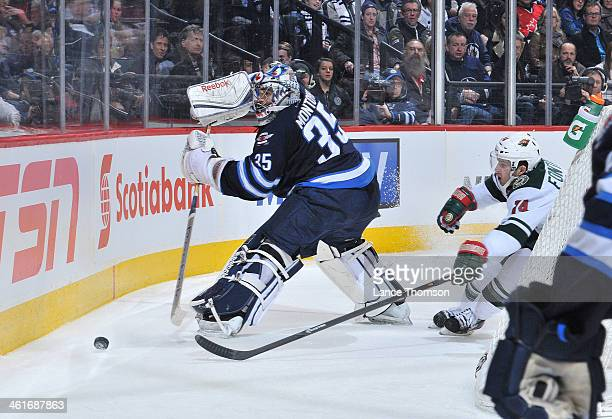 Goaltender Al Montoya of the Winnipeg Jets backhands the puck behind the net away from Justin Fontaine of the Minnesota Wild during third period...