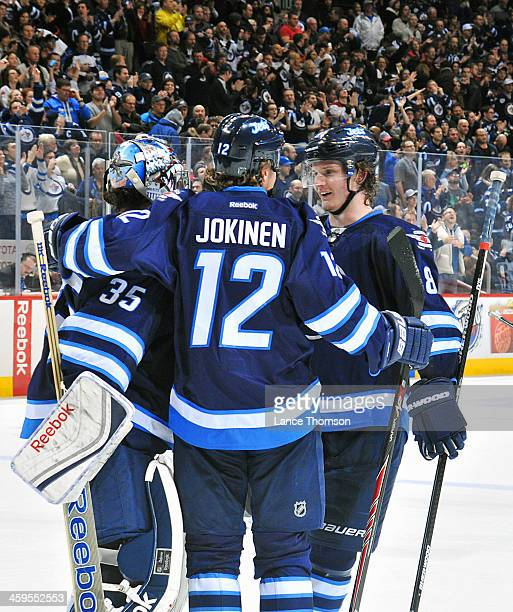 Goaltender Al Montoya of the Winnipeg Jets gets congratulated by teammates Olli Jokinen and Jacob Trouba after backstopping the Jets to a 64 victory...