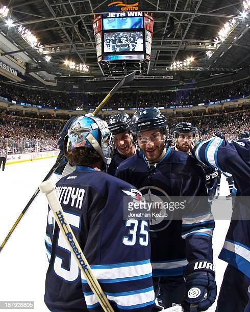 Goaltender Al Montoya of the Winnipeg Jets gets congratulations from teammate Anthony Peluso after backstopping the Jets to a 42 victory over the...