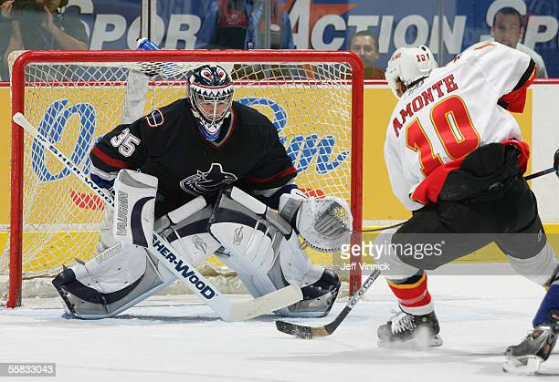 Goaltender Alex Auld of the Vancouver Canucks watches as Tony Amonte of the Calgary Flames is hooked from behind on a breakaway during their...