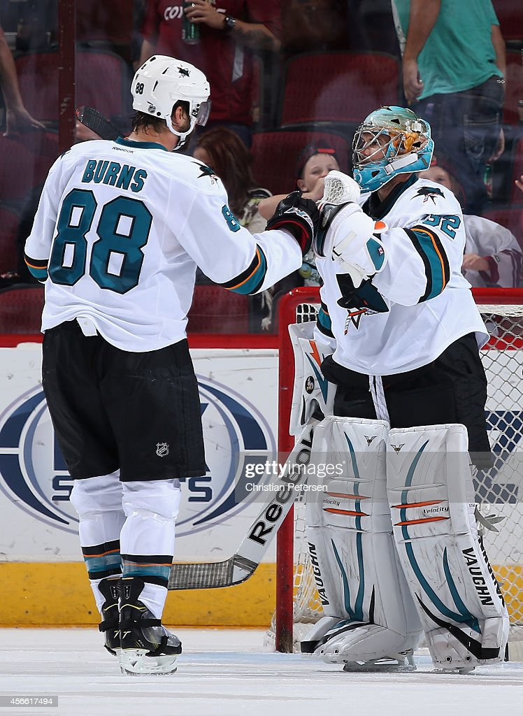 Goaltender Alex Stalock #32 of the San Jose Sharks is congratulated by Brent Burns #88 after defeating the Arizona Coyotes in the preseason NHL game at Gila River Arena on October 3, 2014 in Glendale, Arizona. The Sharks defeated the Coyotes 3-1.