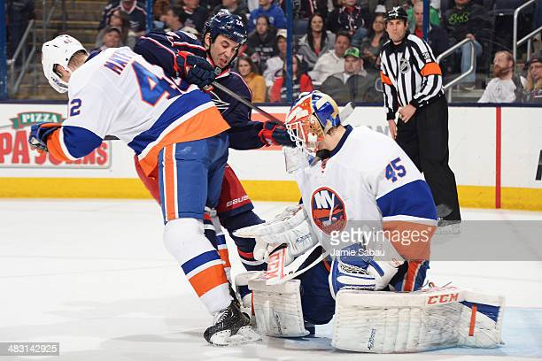 Goaltender Anders Nilsson and Scott Mayfield of the New York Islanders defend the net against Derek MacKenzie of the Columbus Blue Jackets during the...