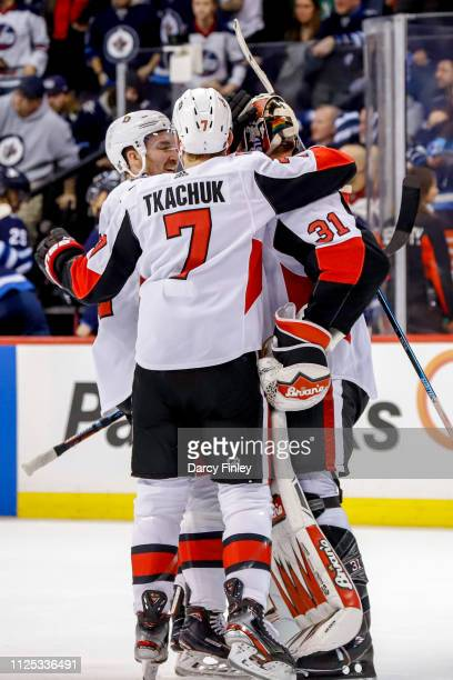 Goaltender Anders Nilsson of the Ottawa Senators gets congratulated by teammates Mark Stone and Brady Tkachuk following a 43 overtime victory over...